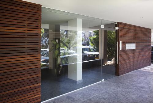 ויטרינת כניסה מזכוכית על קיר עץ