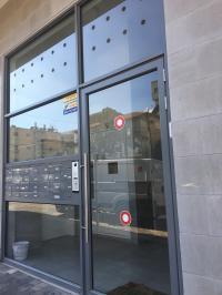 דלת אלומיניום עם פתחי איוורור ותיבות דואר בויטרינה